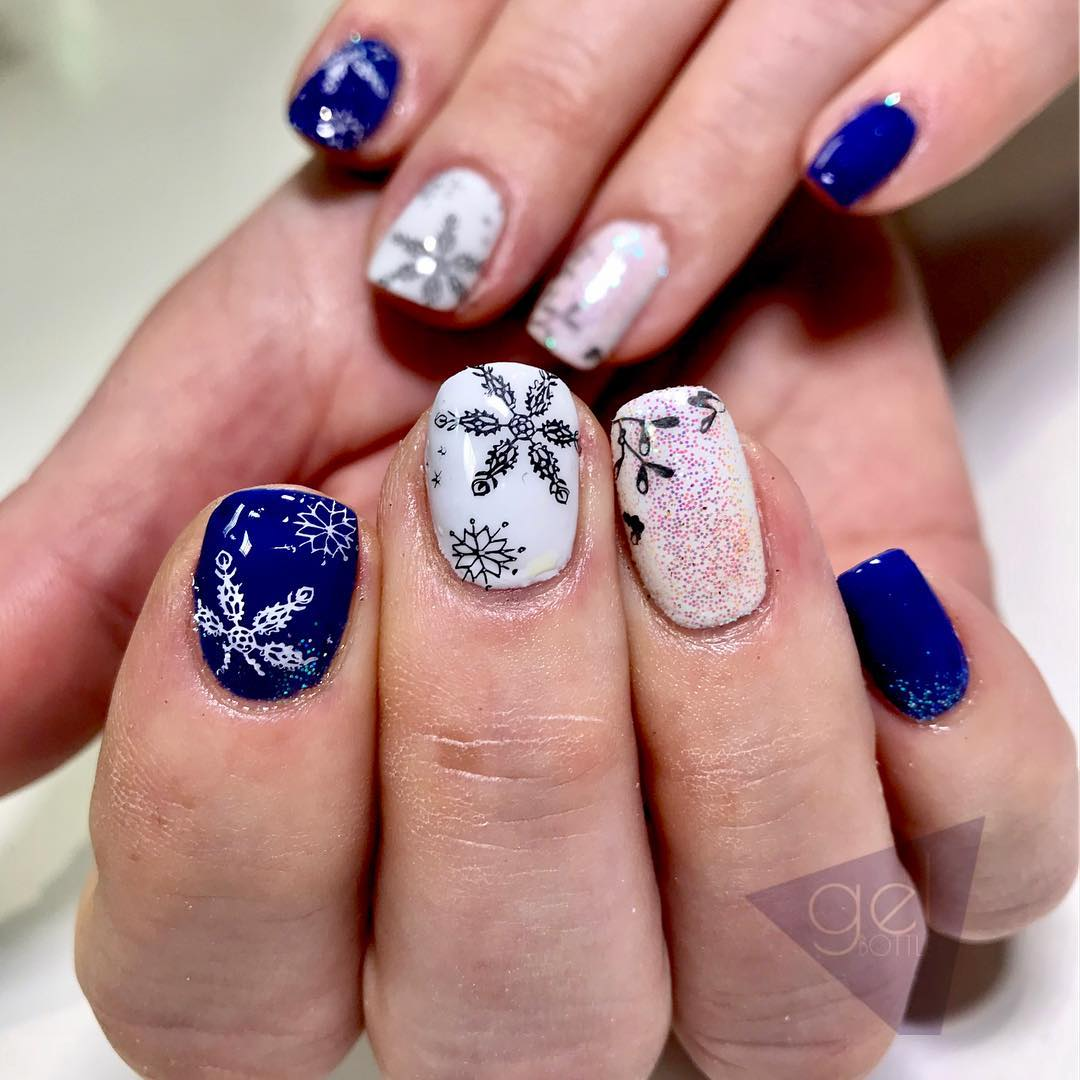 Blue and white nails with snowflakes. Pic by oasisbeautyandnails_