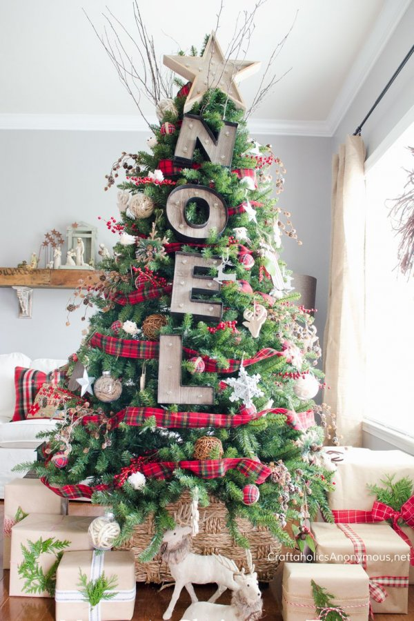 Christmas tree is decorated with golden ornaments, marquee letters, plaid ribbon and woodland creatures.