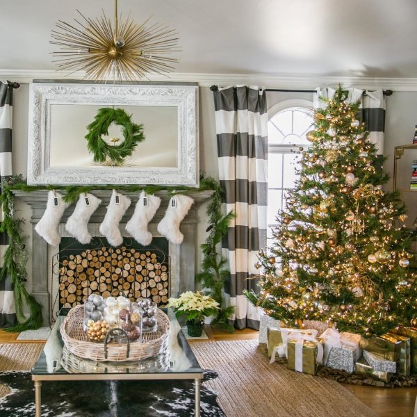 Golden lighting on Christmas tree, Striped curtains, white Christmas socks and fire place. Pic by amyspearinginteriors