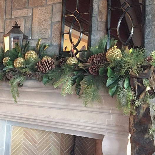 Magnolia, pine cones and burnished gold balls with mirrors and lanterns for mantel decor. Pic by happinest_designs