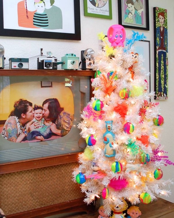 Pretty white Christmas tree decorated with colorful toys. Pic by treetopia