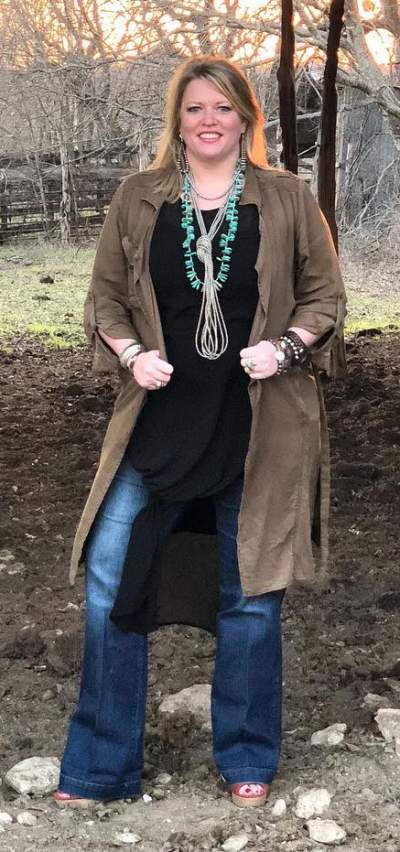 Brown Coat, Black Long Top With Blue Jeans And Necklace