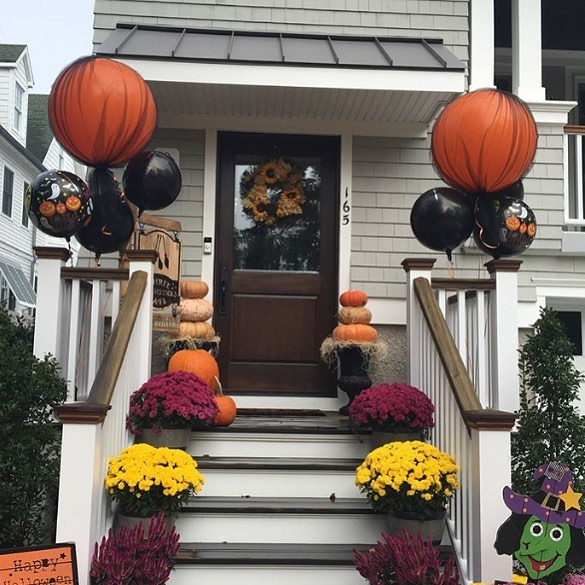 Front Door Is Decorated With Orange And Black Balloons And Flowers