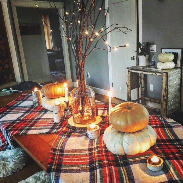 Dry tree branches, pumpkin and plaid table cover looks amazing