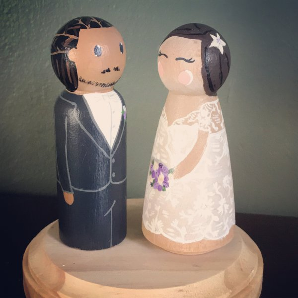 Rocking haircut of groom with beautifully dresses bride wedding cake toppers