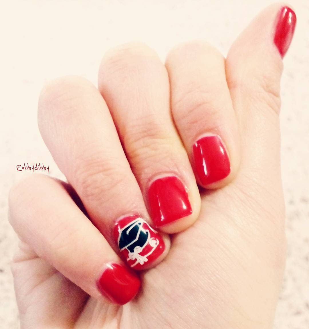 Short red nails with graduation cap. Pic by robbydibby