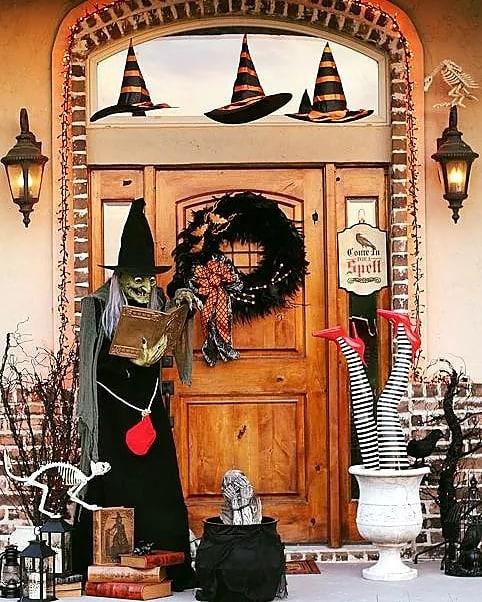 Amazing outdoor decor with witch. floating hats and dry tree branches.