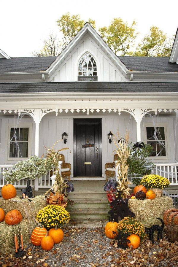 Classic country Halloween decor on your front porch by arranging hay bales, mums, pumpkins, dried corn stalks and fake spiderweb
