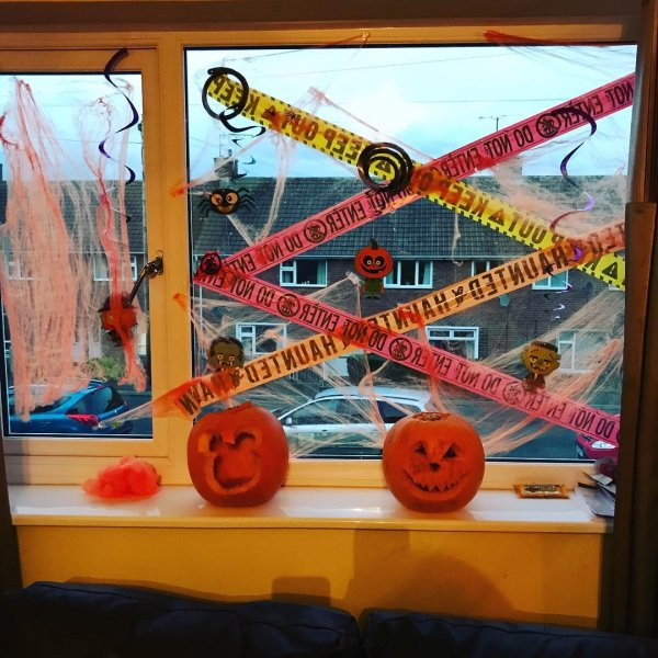 Crime scene with trick or treat pumpkin decor at window.