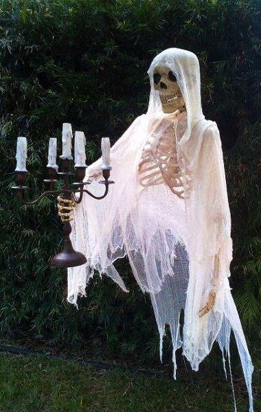Floating skeleton holding candles.