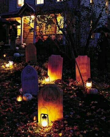 Front yard is setup as graveyard decorated with pumpkins and lanterns.