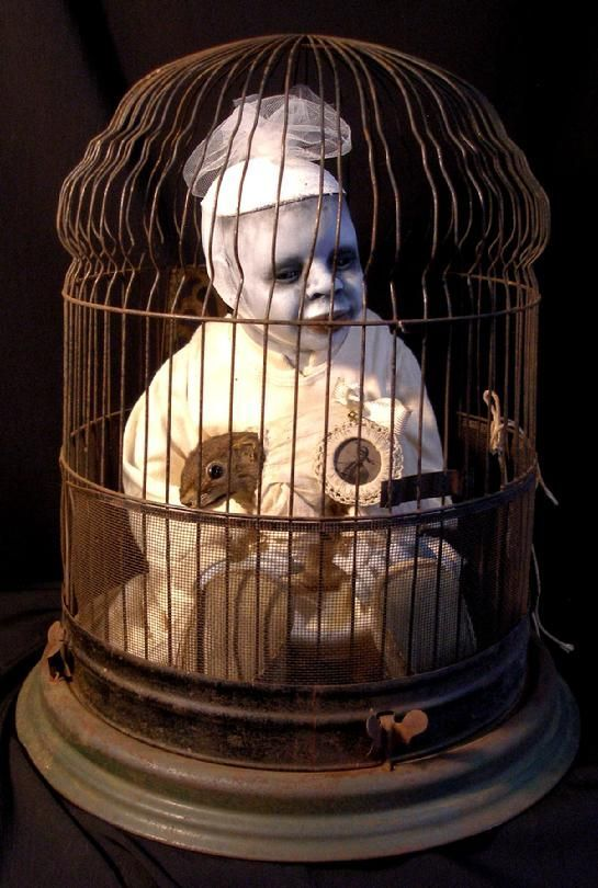 Ghastly white and creepy and put inside a bird cage.