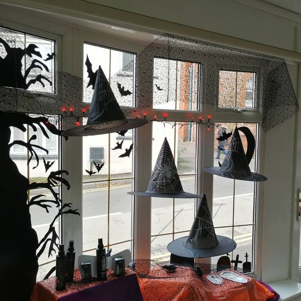 Hanging witch hats, bats, mice and spooky tree for Halloween window decoration.