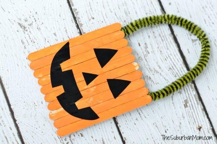 Homemade pumpkin popsicle stick door hanger for halloween.