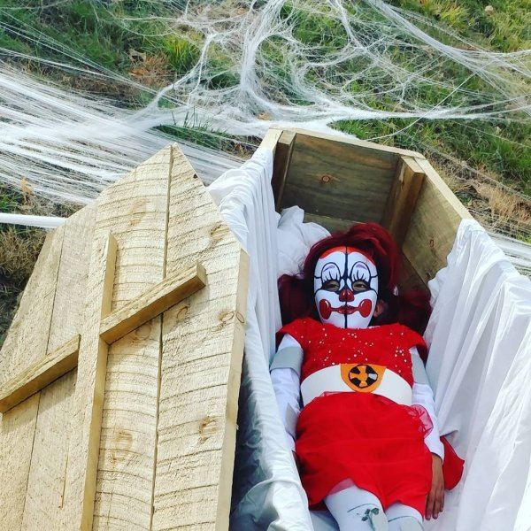 Killer clown lying in coffin.
