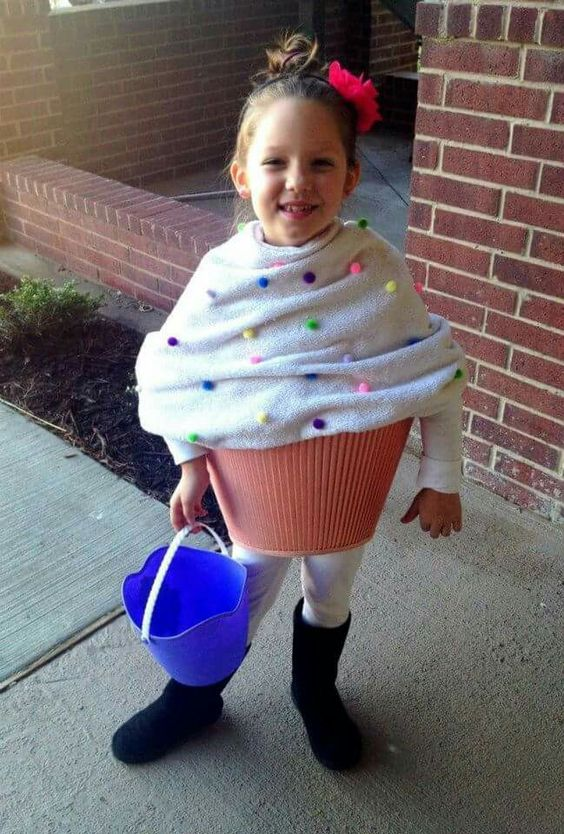 Little girl is dress up as cup cake.
