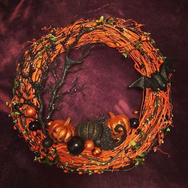Orange and black wreath with cat, bat and pumpkins.