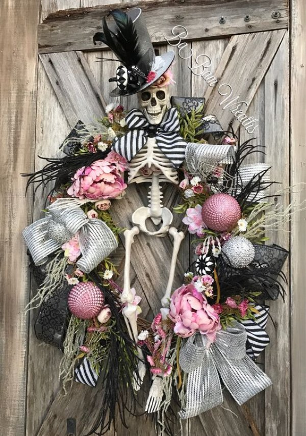 Pink and black Halloween wreath with skeleton.