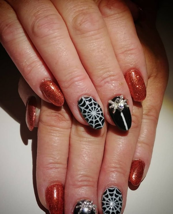 Pretty black and orange glitter spider web nails. Pic by clarabellabeautybar