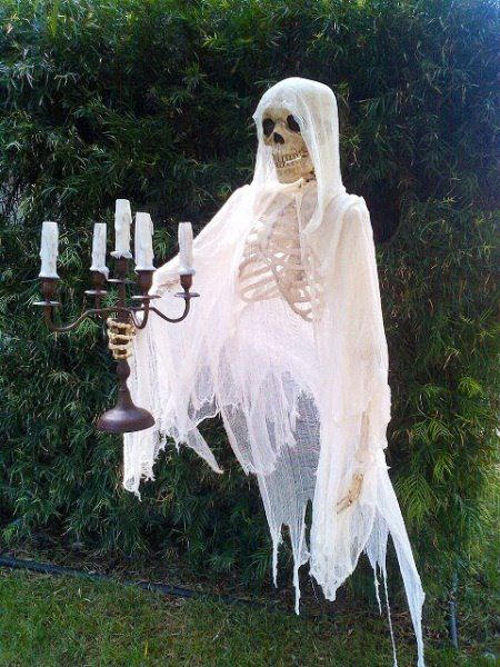 Skeleton covered with clothes holding candle holder.