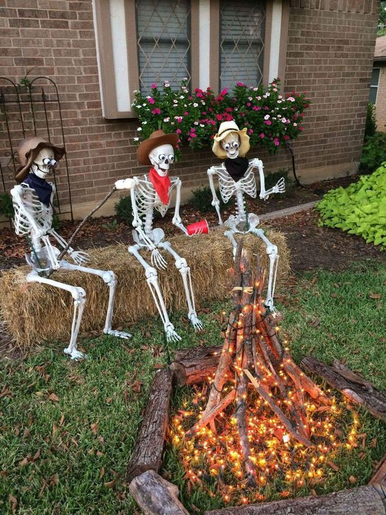 Skeleton enjoying Halloween party, sitting in backyard in front of fire pit.