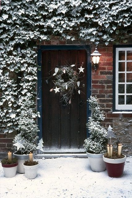 A snowy door way with frosty topiaries and candles.