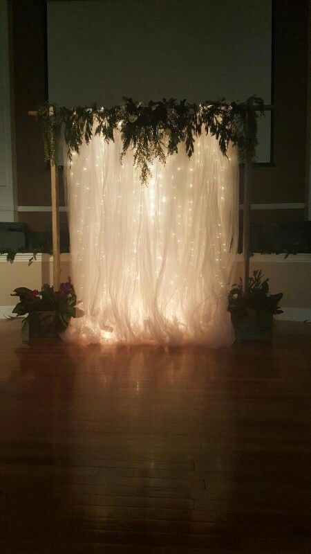 Adorable white shear cloth with lights and herb garland for photo booth.