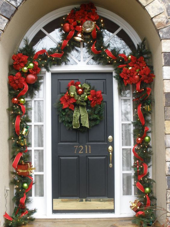 Amazing red and green garland and wreath on front door.