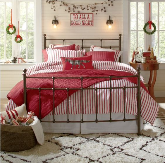 Amazing red and white theme bedroom decor at Christmas with garland and wreath hanging on window.
