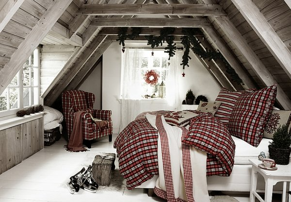 Attic bedroom with pot Christmas tree, natural green garland and checked bedding.