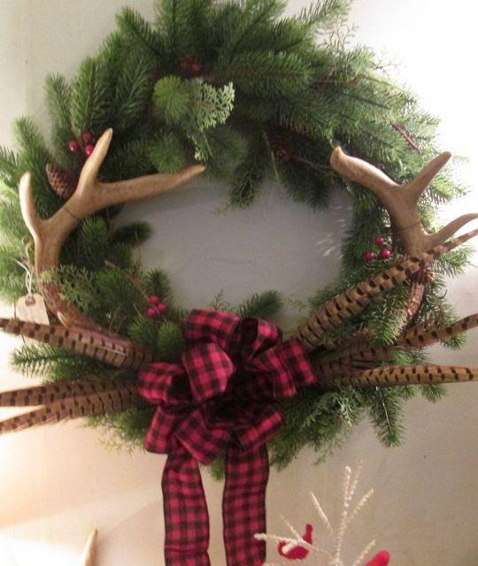Beautiful Christmas wreath with deer antlers and pheasant feathers.