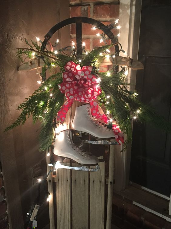 Beautiful old wooden sled decor made with fresh greenery, lights & childrens ice skates
