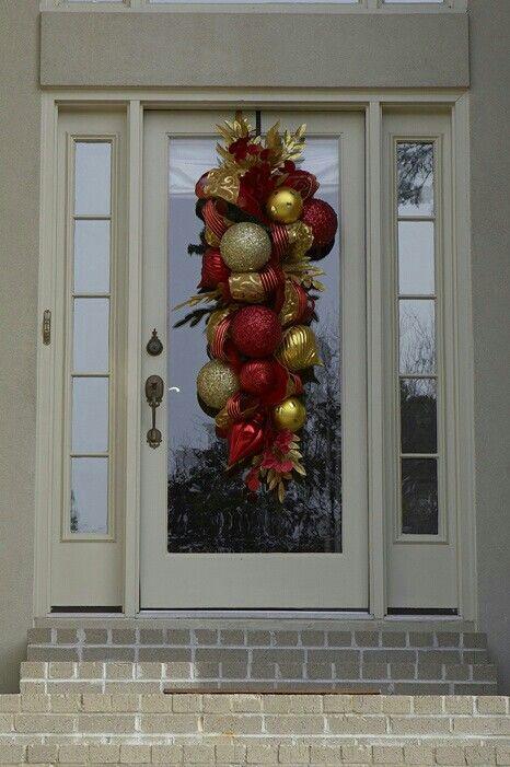 Big red and golden ornament wreath on front door.