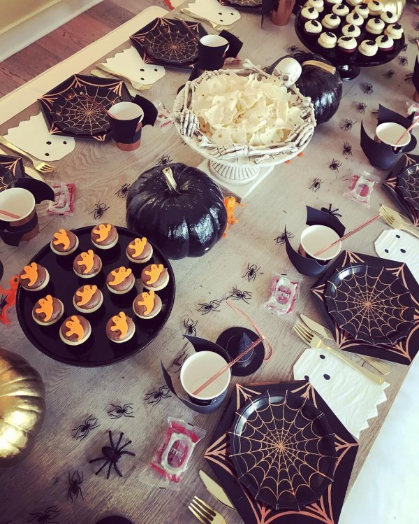 Black and white table decor with creepy decorated snacks and spider web print plates all are perfect for kids Halloween party.