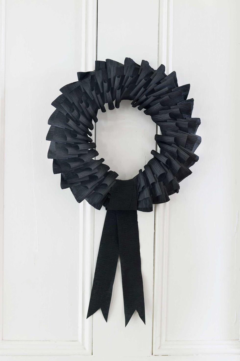 Black crepe paper wreath for door decor.