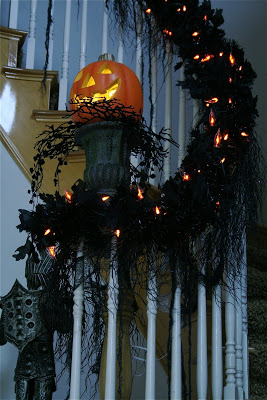 Black garland, orange light and string around banister to create a spooky nighttime glow.