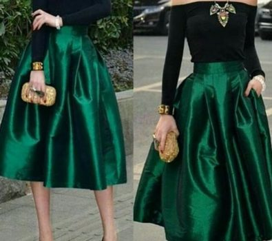 Black off shoulder full sleeves top, deep green satin skirt, necklace, golden clutch and bracelet.