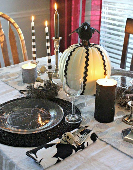 Bug plates, snake nest, pumpkin and skull on table for halloween table decor.