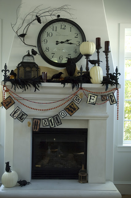 Charming clock centered mantel decor for halloween.