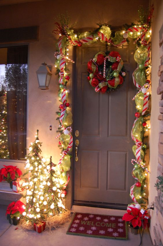 Charming front door decor with garland, green ribbon wreath and Christmas tree decorated with lights.