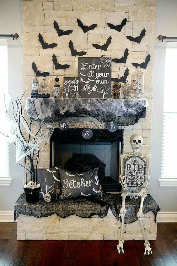 Classic Halloween Mantel decor with flying bats, tree and skeleton.