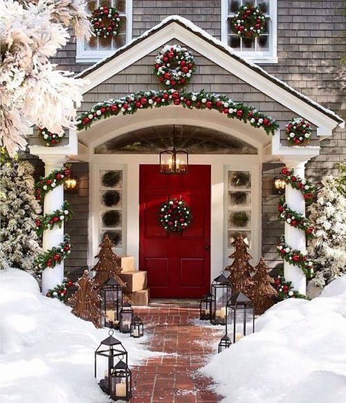 Classic front porch decoration with with wreath , garland decorated with red and green balls and rustic trees.