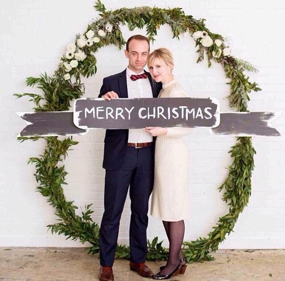 Dashing wreath photo booth with chalkboard banner sign.