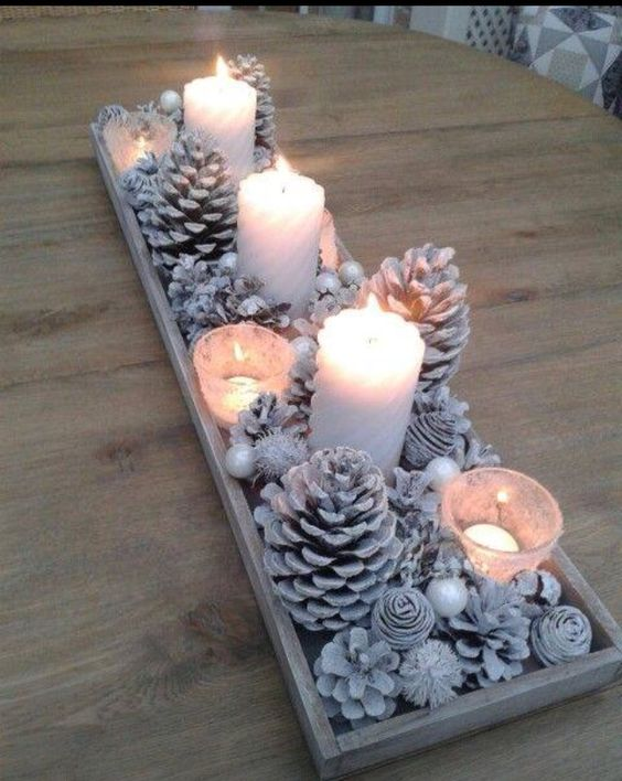 Exclusive candle decor with pinecones in a tray.