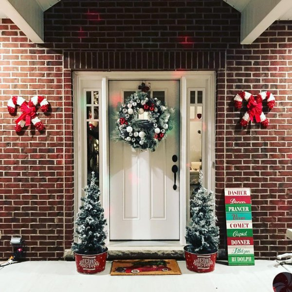Farmhouse style porch decoration with wreath, jtree and Candies on wall.