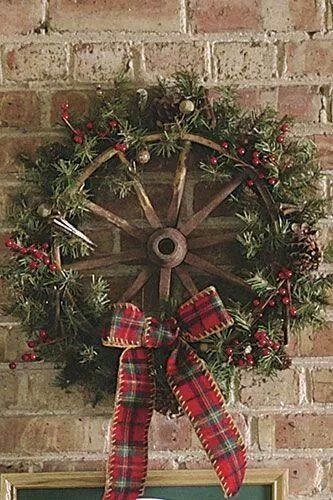 Farmhouse style wreath made by wheel and decorated with red berries and ribbon.
