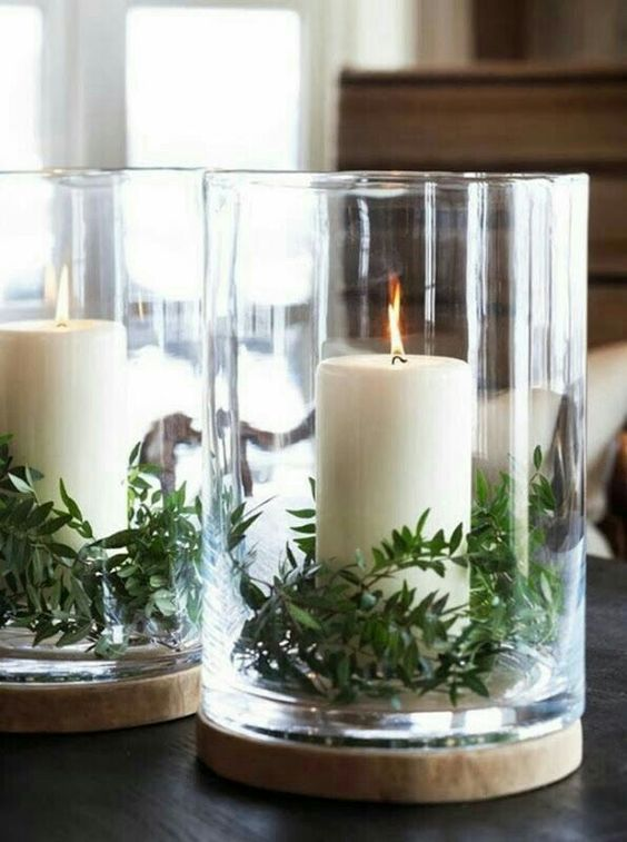 Fir tree leaves in glass box and candles.