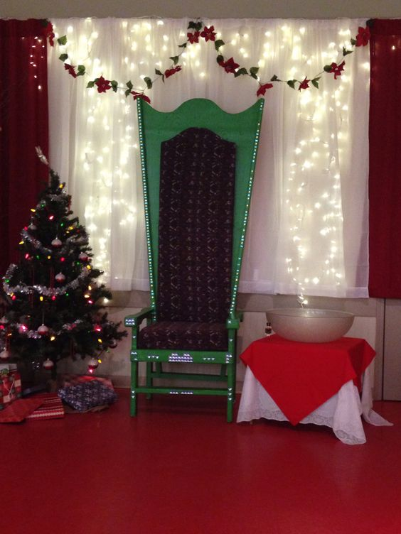 fresh flower garland white lights christmas tree and big green chair for backdrop at