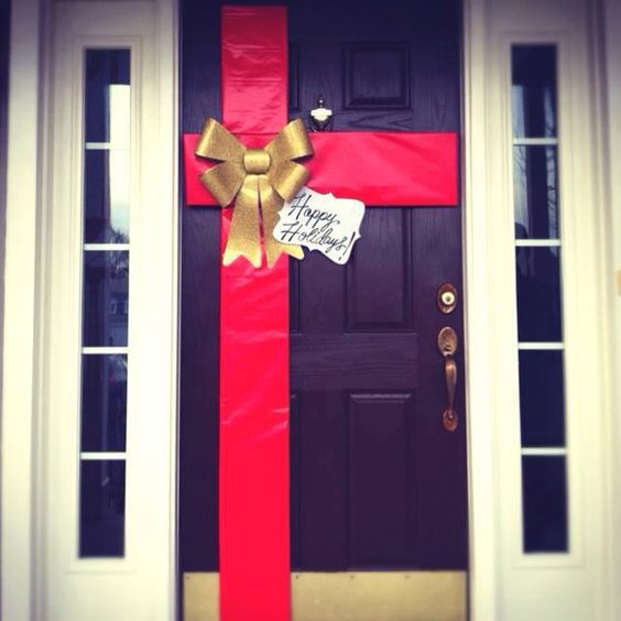 Front door is decorated with red ribbon as gift.