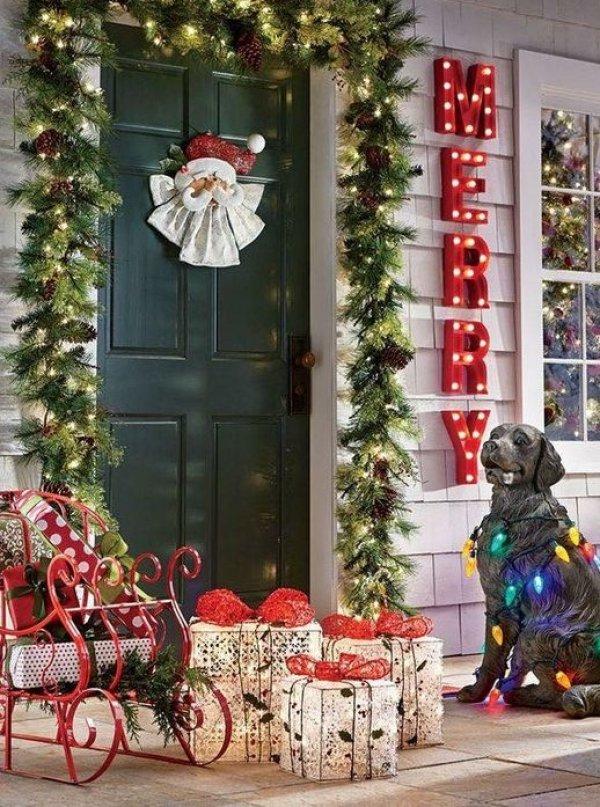Garland with light on front door with Santa on door.